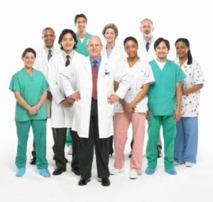 Group of doctors and nurses standing on white background, smiling.